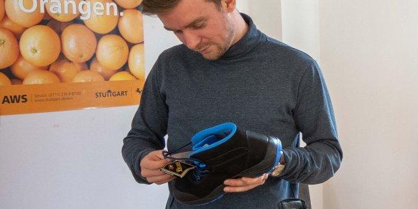 Bedarfsträger mustern beim Workshop die neuen Schuhe und informieren sich über die Herstellungsbedingungen. Foto © FEMNET