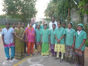 Junge Frauen in einer Spinnerei in Tamil Nadu, dahinter stehenMagnus Schmid (GIZ), Gisela Burckhardt (FEMNET) und Mr. Aloysius (NGO SAVE). Foto: © FEMNET
